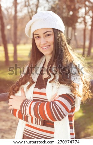 Cheerful Beautiful Lovely Young Woman Relaxing in the park. Autumn or winter season outdoor people portrait. - stock photo