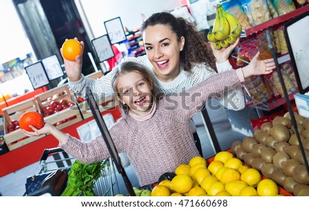 Cheerful beautiful mother and smiling little girl choosing fresh fruits in grocery