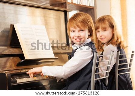 Cheerful beautiful small girls play piano together - stock photo