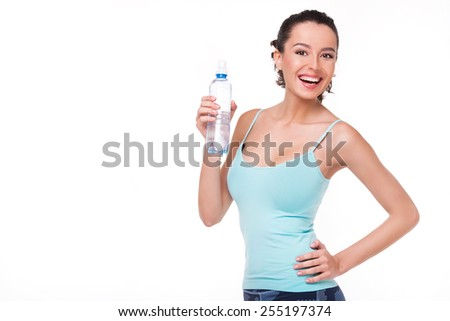 Cheerful beautiful sporty woman holding a bottle of water, isolated on white background - stock photo