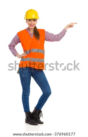 Cheerful beautiful woman in yellow hardhat, orange reflective vest, lumberjack shirt, jeans and black boots, pointing and looking at camera. Full length studio shot isolated on white.