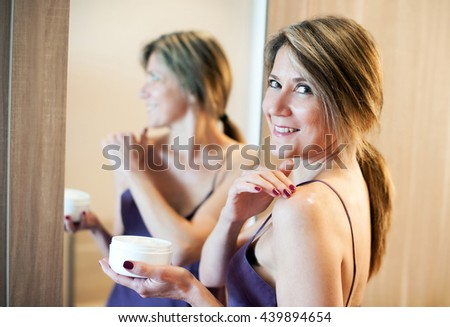 Cheerful beautiful woman with long hair and purple night gown looking back from mirror while applying cosmetic or sun block cream on shoulder - stock photo