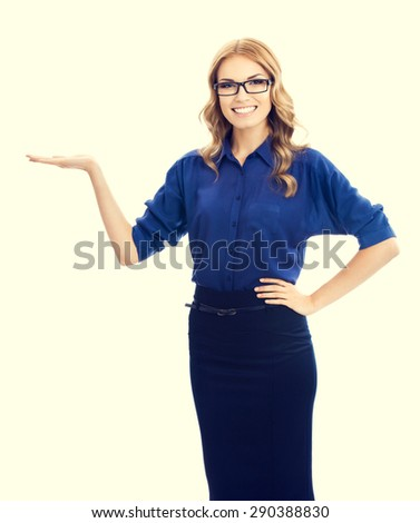 Cheerful beautiful young businesswoman in blue clothing showing something or blank copyspace area for slogan or text message - stock photo