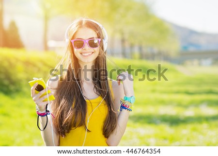 Cheerful beautiful young millennial blonde woman listening to music on headphones, holding smartphone, outdoors in park on sunny summer day. Vibrant colors, natural light. - stock photo