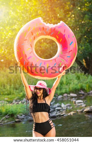 Cheerful beautiful young millennial woman holding sprinkled pink inflatable donut float in summer, standing in the river in nature smiling, wearing black bikini, sunglasses and hat. Vibrant colors. - stock photo