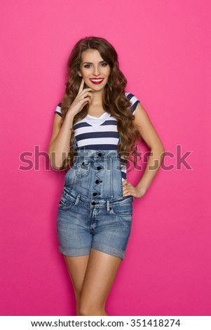 Cheerful beautiful young woman in dungarees holding hand on chin and looking at camera. Three quarter length studio shot on pink background. - stock photo