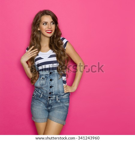Cheerful beautiful young woman in dungarees looking at copy space. Three quarter length studio shot on pink background. - stock photo