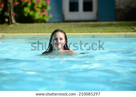 cheerful beautiful young woman in resort swimming pool during summer vacations
