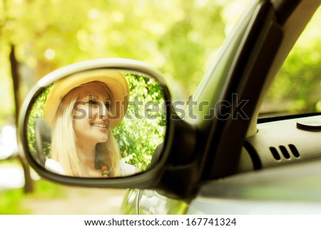 Cheerful beautiful young woman in the car, reflection in the mirror. - stock photo