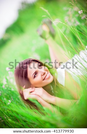 Cheerful beautiful young woman lying among the grass and flowers - stock photo