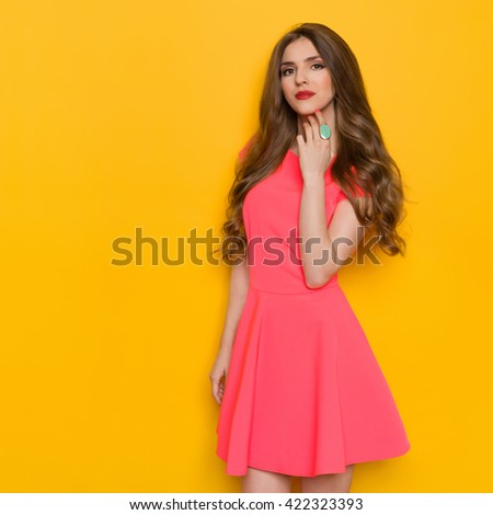 Cheerful beautiful young woman with curly long brown hair posing in pink mini dress and holding hand on chin. Three quarter length studio shot on yellow background.