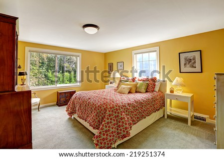 Cheerful bedroom interior in bright yellow color and red bedding - stock photo