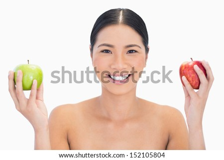 Cheerful black haired model holding apples in both hands on white background