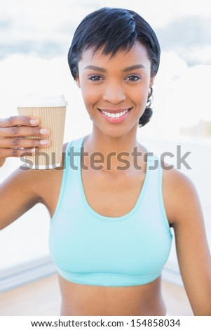 Cheerful black haired woman drinking coffee in a living room