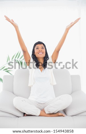 Cheerful black haired woman in white clothes raising her arms in a living room - stock photo