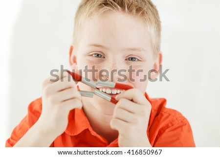 Cheerful blond and green eyed boy wearing a red shirt holds two magnets together by his face