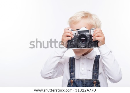 Cheerful blond boy is standing and holding old camera. He is photographing something with interest. Isolated and copy space in left side - stock photo