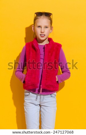 Cheerful blond girl in pink fur vest posing with hands in pockets. Three quarter length studio shot on yellow background. - stock photo