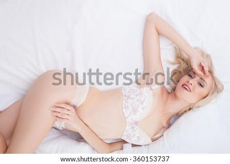 Cheerful blond girl is relaxing in underwear