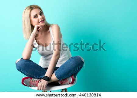 Cheerful blond girl is sitting with anticipation - stock photo