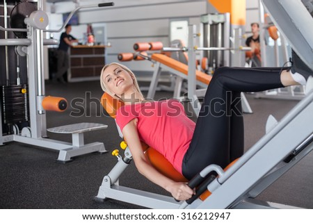 Cheerful blond girl is training with the equipment in fitness center. She is lying on bench and raising her legs. The sportswoman is looking aside and smiling