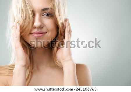 cheerful blond girl straightens her hair