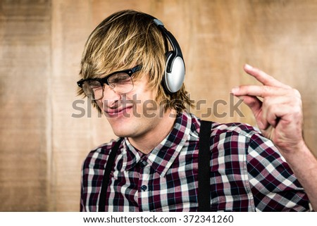 Cheerful blond hipster listening to music with wooden background - stock photo