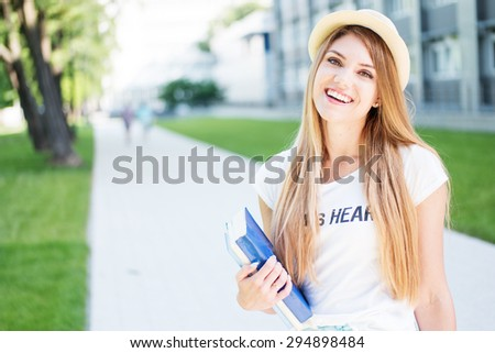 Cheerful Blond Student Teen Girl in Casual Outfit, Holding Books and Smiling at the Camera While Standing at the Outdoor Walkway. - stock photo