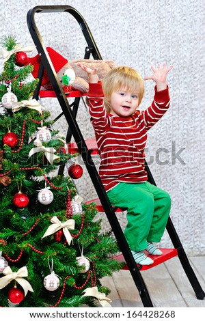 Cheerful blond toddler sitting on the ladder with his hand up by the Christmas tree