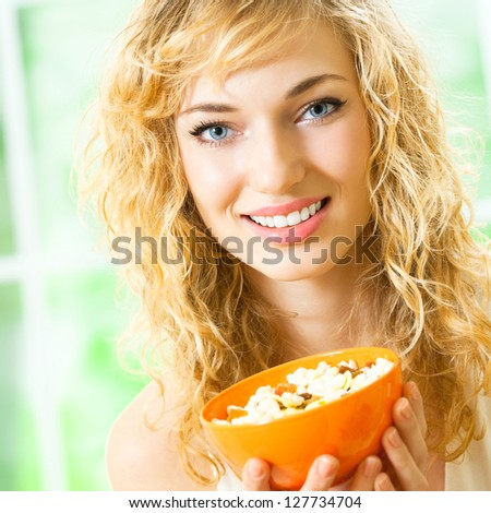 Cheerful blond woman eating cereal muslin - stock photo