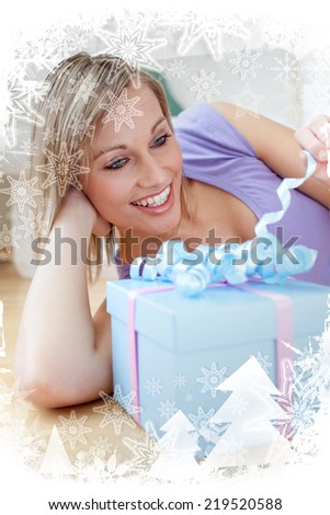 Cheerful blond woman holding a present lying on the floor against christmas frame - stock photo