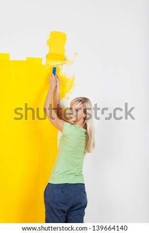 Cheerful blond woman painting wall with roller - stock photo