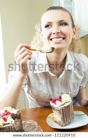 Cheerful blond young woman eating torte, indoors - stock photo