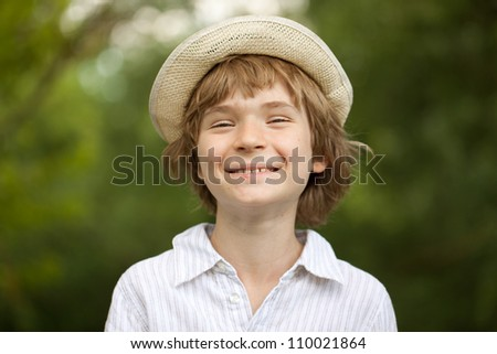 Cheerful blonde boy in a straw hat - stock photo