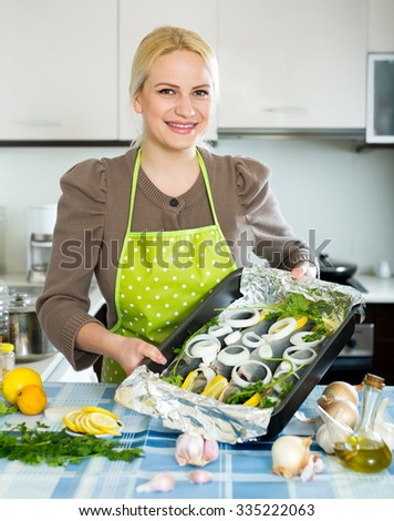 Cheerful blonde girl cooking fish  in frying pan at home kitchen