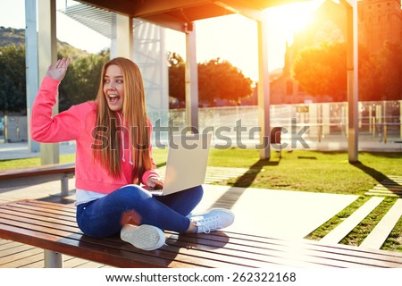 Cheerful blonde hair female student waving to someone sitting on the campus bench at beautiful sunny day, happy female teenager greeting hello while sitting with open laptop outdoors, flare bright sun - stock photo