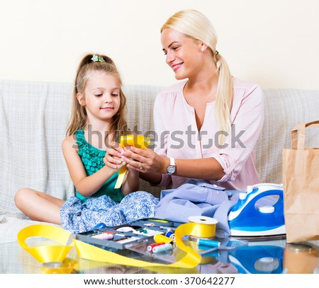 Cheerful blonde mother and little daughter working with textile indoors