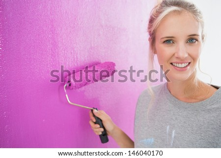 Cheerful blonde painting her wall pink and smiling at camera in new home - stock photo