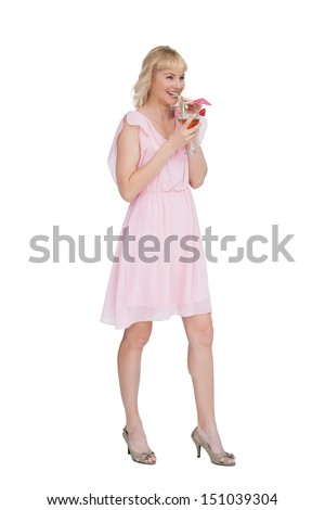 Cheerful blonde posing while drinking cocktail against white background - stock photo