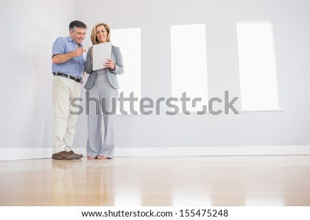 Cheerful blonde realtor showing an empty room and some documents to a potential attentive mature buyer - stock photo