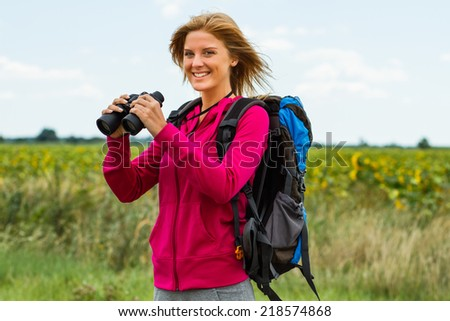 Cheerful blonde woman is standing in the nature and holding binoculars ,Enjoying nature with binoculars - stock photo