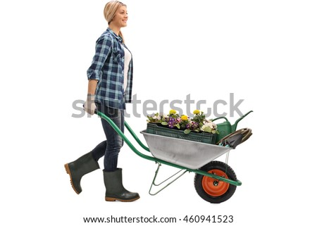 Cheerful blonde woman pushing a wheelbarrow with gardening equipment isolated on white background