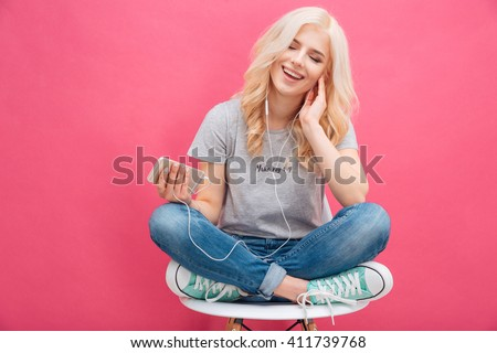 Cheerful blonde woman sitting on the chair and listening music in headhpones over pink background - stock photo