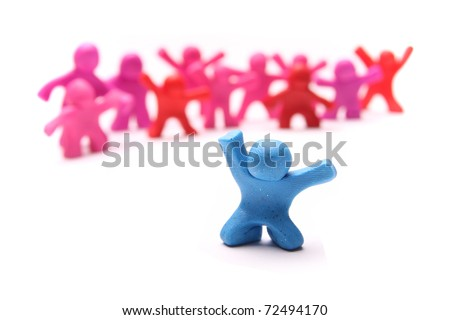 cheerful blue plasticine boy standing out of a group of pink girls
