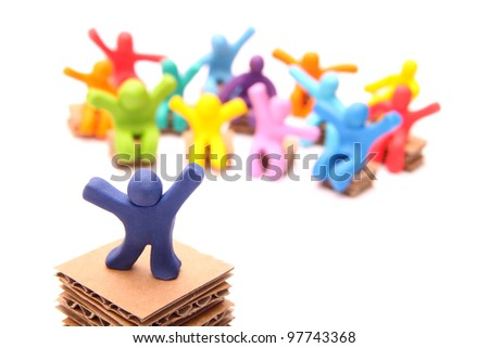 cheerful blue plasticine guy standing on podium in front of his colorful audience sitting on paper chairs - isolated on white - stock photo