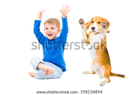 Cheerful boy and dog together with hands raised - stock photo