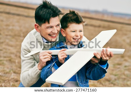 Cheerful boy and his father playing with toy airplane outside - stock photo