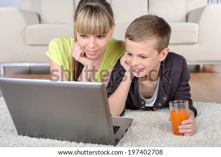 Cheerful boy and mother lying on floor using laptop at home in living room