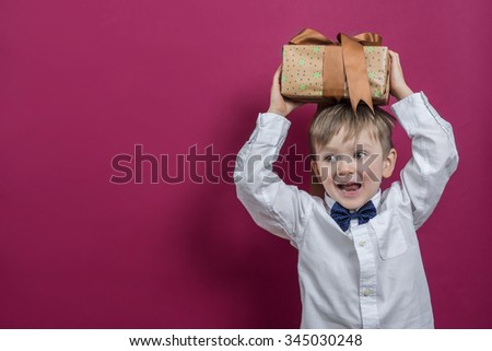 Cheerful boy holding a present. - stock photo