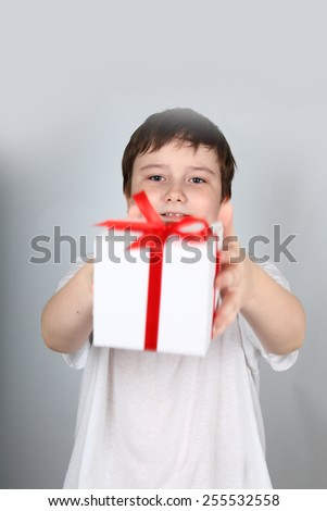 Cheerful boy in a white shirt holding a gift